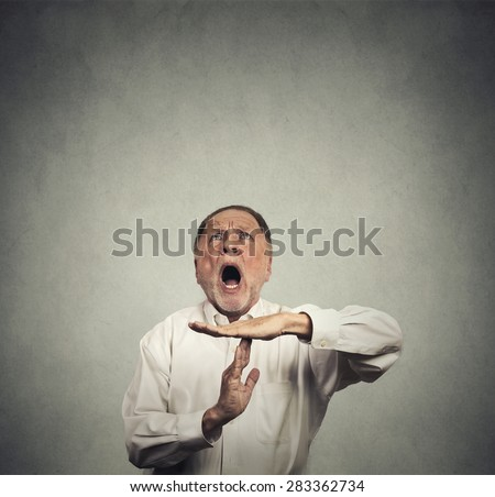 Elderly man boss showing time out hand gesture, frustrated screaming to stop looking up isolated on grey wall background. Too many things to do. Human emotions face expression reaction - stock photo