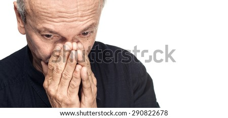Elderly man covers his face with hand isolated on white background with copy-space