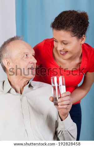 Elderly man drinking water and his granddaughter - stock photo