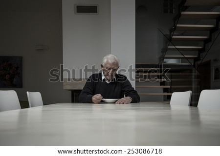 Elderly man eating dinner completely alone in huge house - stock photo