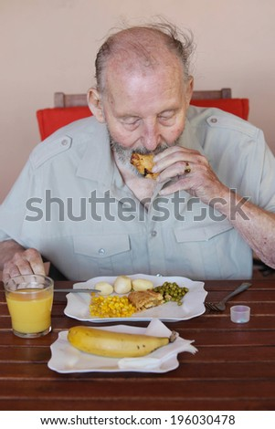 elderly man eating healthy lunch in care home - stock photo