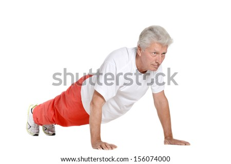 Elderly man exercising in a gym isolated on white background - stock photo