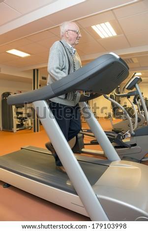 Elderly man exercising on a treadmill for his rehabilitation - stock photo