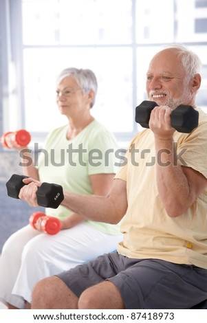 Elderly man exercising with dumbbells at gym.? - stock photo