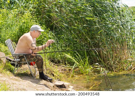 Elderly man fishing on a lake carefully testing his line for a bite as he sits patiently in a chair at the edge of a lake