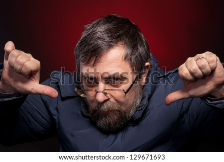 Elderly man gives thumbs down on a red background