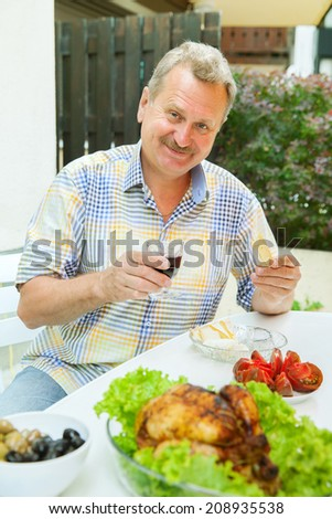 elderly man has lunch on the patio