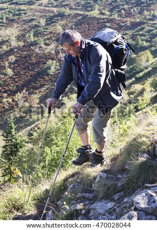 Elderly man hiking in the mountains with backpack and nordic poles.