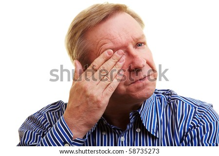 Elderly man holding hand over his aching eye