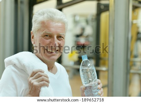 Elderly man in a gym. drinking water after exercise - stock photo