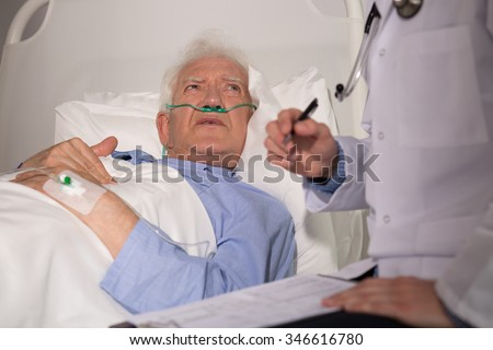 Elderly man in bed examined by doctor  - stock photo