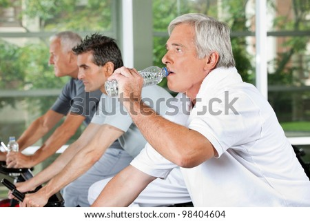 Elderly man in fitness center drinking water from a plastic bottle - stock photo