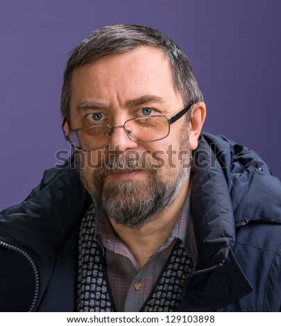 Elderly man in glasses on a violet background