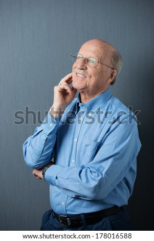 Elderly man in glasses standing thinking with his hand to his chin and a happy smile as he recalls fond memories - stock photo