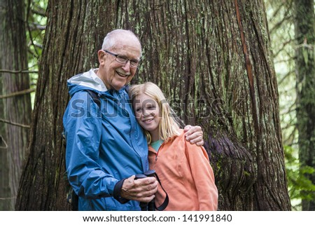 Elderly man in his 80s standing by a cabin - stock photo