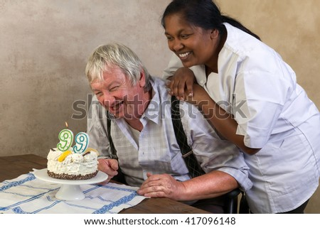 Elderly man in nursing home blowing out candles on his birthday cake