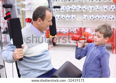elderly man in shop on  sports exerciser and boy with barbell in hand, focus on senior - stock photo