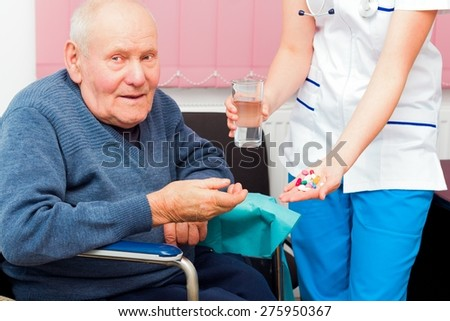 Elderly man in wheelchair taking several medications from kind nurse.