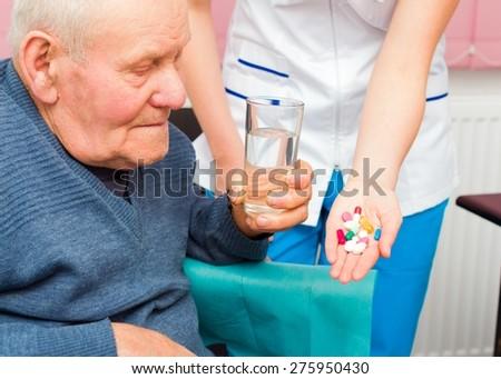 Elderly man in wheelchair taking several medicine from kind nurse. - stock photo