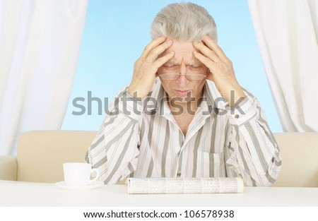 Elderly man is reading the newspaper at home - stock photo