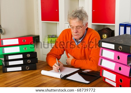 Elderly man is sitting with many paper folders and writing a letter - stock photo
