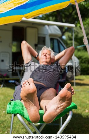 Elderly man is sleeping at the camping with bare feet (focus on feet) - stock photo