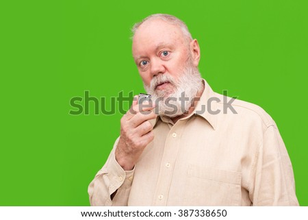 Elderly man is speaking to voice recorder on green background, portrait, color and contrast manipulated - stock photo