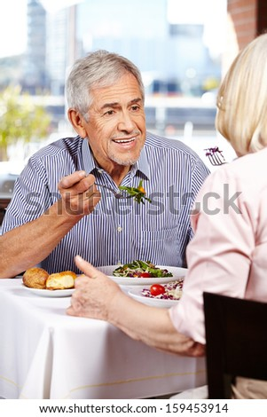 Elderly man listening to his wife in a restaurant while eating - stock photo