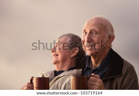 Elderly man looking over with companion outdoors - stock photo