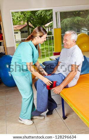 Elderly man moving his legs at physiotherapy with the help of physiotherapist - stock photo