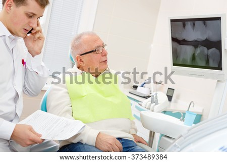 Elderly man on a review of a dentist, sitting in a chair. - stock photo