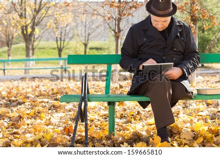 Elderly man on crutches using a tablet computer as he sits outdoors in the sunshine in a warm overcoat on a chilly autumn day - stock photo