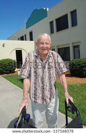Elderly man outside assisted living center. - stock photo