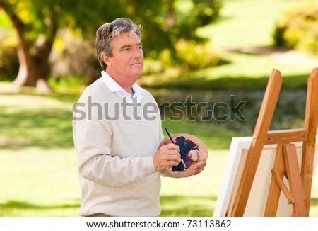Elderly man painting in the park