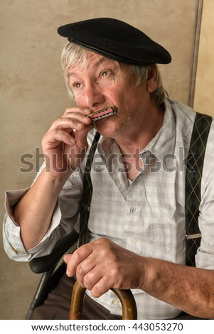 Elderly man playing his harmonica holding his cane - stock photo