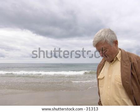 Elderly man pondering by the ocean. - stock photo