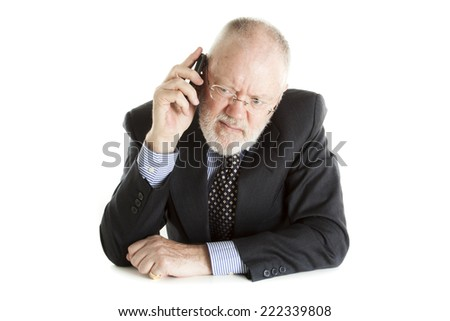 Elderly man posing on white background and having annoying phone call - stock photo