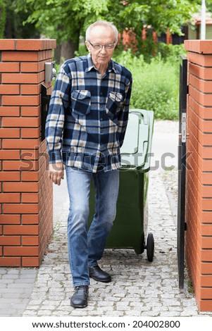 Elderly man pulling a wheeled dumpster, vertical - stock photo