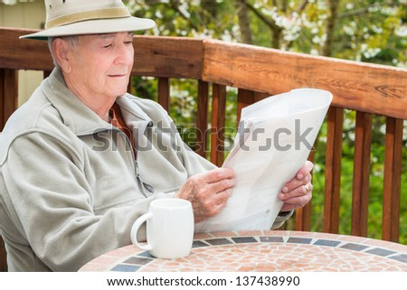 Elderly Man Reading Newspaper and Drinking Coffee - stock photo