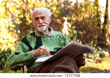 Elderly man reading the newspaper and drinking coffee outdoors.