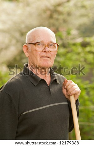 Elderly man relaxing after work in garden - stock photo