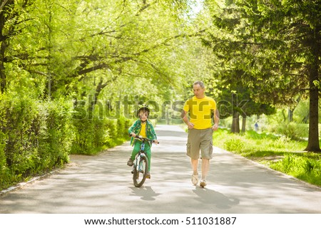 Elderly man runs together with her grandson, who rides a bike
