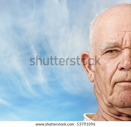 Elderly man's face over blue sky - stock photo