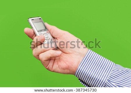 Elderly man, senior, is holding voice recorder on green background, color and contrast manipulated - stock photo