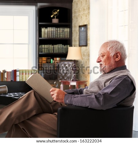 Elderly man sitting in armchair reading book at study at home. - stock photo