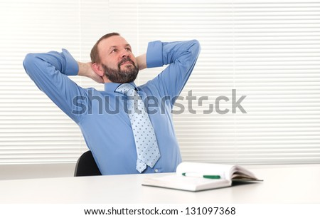 elderly man sitting in his office - stock photo