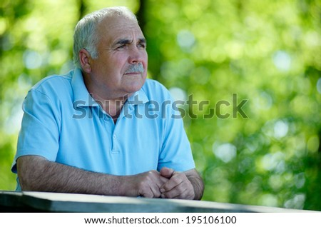 Elderly man sitting in the garden at a wooden table thinking and staring into the distances as he reminisces fond memories, with copyspace - stock photo