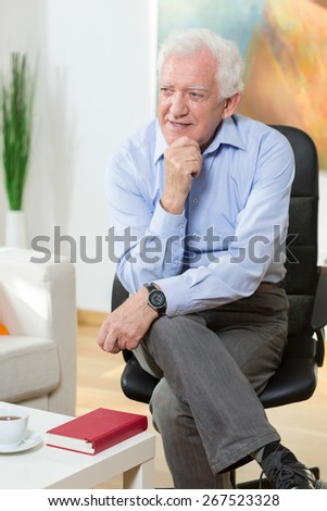 Elderly man sitting on a chair and smiling - stock photo