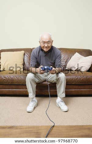 Elderly man sitting on couch playing video games