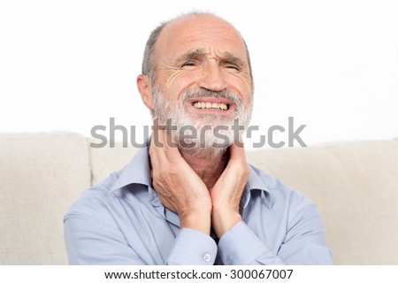 Elderly man sitting suffering from throat problems